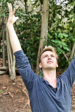 raises: man wearing a long sleeve blue t-shirt raises his arms toward the sky in a salutation yoga pose Stock Photo