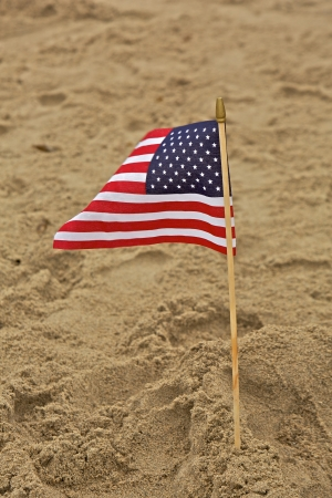 A small American flag is planted into the sand at a beach