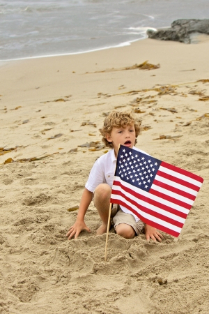 A young blond boy plants the American flag into the sand while playing at the beach