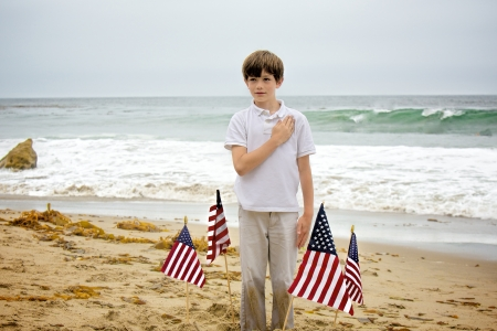 A young boy, with sand all over his hands and pants, plants four American flags into the sand at the beach then stands among them with his hand to his heart