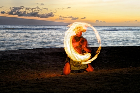 A male fire dancer kneels on a Hawaiian beach at dusk, spins a stick with fire to create a glowing circle of fire in the air   Zdjęcie Seryjne