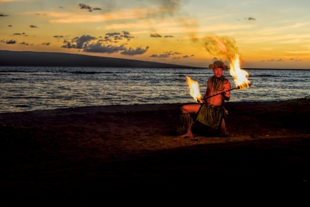 Bathed in an orange glow, a male fire dancer kneels on a Hawaiian beach at dusk, holds a stick with fire on either end, as flames jump up into the twilight sky