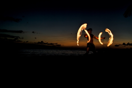 A male fire dancer on a Hawaiian beach spins sticks with fire on to create circles of flames   Zdjęcie Seryjne
