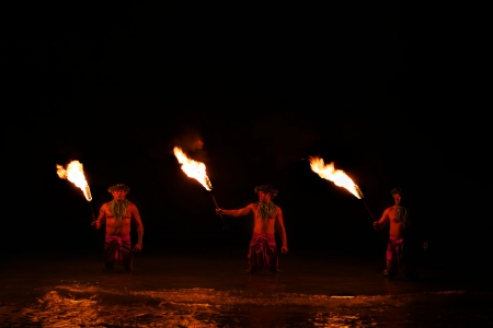 Bathed in an orange glow, three male fire dancers stand in the ocean and hold sticks with fire on one end  The glow of the fire is reflected on the water  Zdjęcie Seryjne