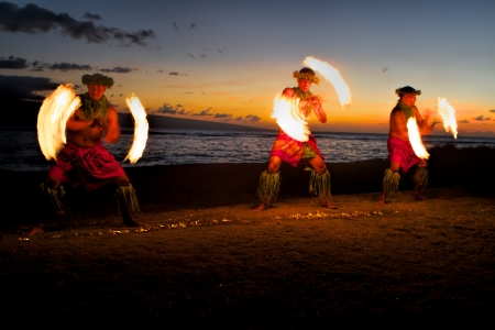 Bathed in an orange glow, three male fire dancers on a Hawaiian beach at dusk, spin sticks with fire on either side, creating patterns in the air  In front of them is a line of fire in the sand