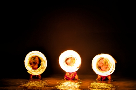Bathed in an orange glow, three male fire dancers on a Hawaiian beach, stand in the ocean up to their knees while quickly spinning sticks with fire on either side, creating giant circles of fire in the air that are also reflected on the water