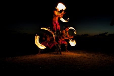 piramide humana: Ba�ado en un resplandor naranja, tres bailarines de fuego macho en una playa hawaiana, crean una pir�mide humana y palos vuelta con fuego a ambos lados El resplandor del fuego ilumina el suelo