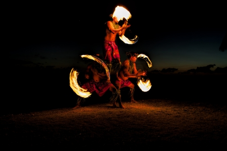 Bathed in an orange glow, three male fire dancers on a Hawaiian beach, create a human pyramid and spin sticks with fire on either side  The glow of the fire illuminates the ground