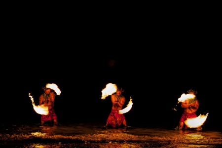 either: Bathed in an orange glow, three male fire dancers on a Hawaiian beach, stand in the ocean up to their knees and spin sticks with fire on either side  The glow of the fire is also reflected on the water  Stock Photo