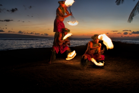Bathed in an orange glow, three male fire dancers on a Hawaiian beach at dusk, spin sticks with fire on either side, creating patterns in the air  The glow of the fire illuminates the ground