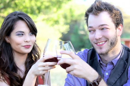 A young 20-something couple clink their wine glasses in a toast