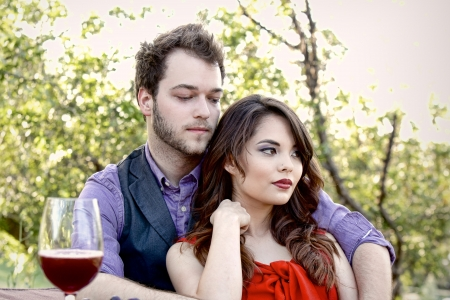 A young 20-something couple relax in a loving embrace while on a picnic in the park