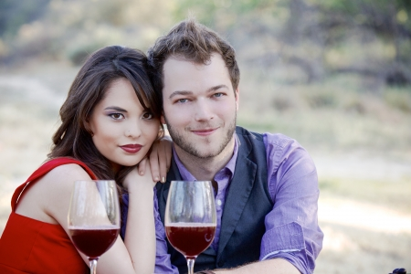 A young 20-something couple are having wine while on a picnic in the park