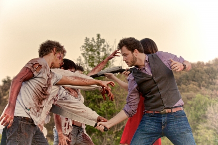 horrific: A man and woman fight off three attacking zombies