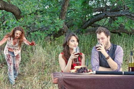 A grotesque and bloody female zombie emerges from the woods and is about to attach an unsuspecting couple having picnic