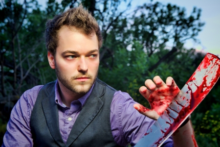 A man stands fearlessly with his bloody machete after killing zombies or something