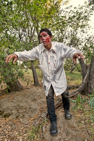 A grotesque and bloody male zombie emerges from the woods