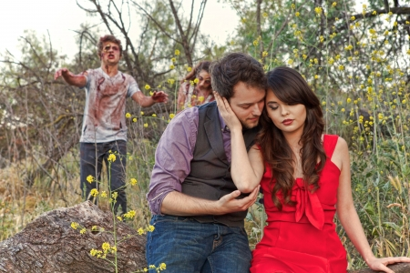 horrific: Two grotesque and bloody zombies slowly walk up behind an unsuspecting couple as they cuddle in a city park Stock Photo