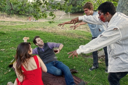 Two grotesque and bloody zombies attack and scare a couple having a picnic in the park
