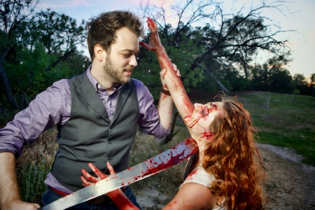 horrific: A mans is about to behead a grotesque and bloody female zombie in a wooded area Stock Photo