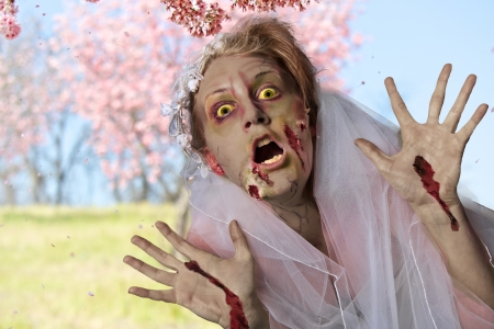 Grotesque and bloody female zombie in a wedding dress and veil stands in a field of spring time cherry blossom trees