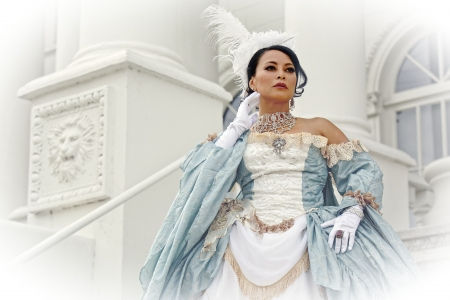 An Asian woman in an old fashioned white and blue dress stands against a white building with ornate architectural details