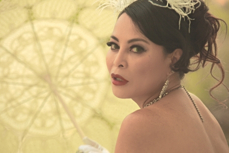 Closeup portrait of Asian woman framed by a parasol with light shining through