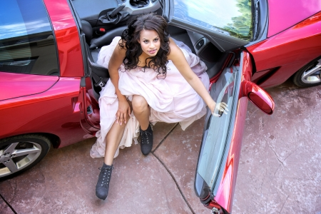 Glamorous young African American woman wearing a bustier and full length puffy pink skirt looks upward while getting out of the passenger seat of a sports car with the top removed photo