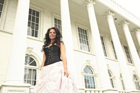 黒のビスチェと全長ふくらんでいるピンク色のスカートを着て華やかな若いアフリカ系アメリカ人女性が白い大きな柱と窓の建物の前でポーズしま 写真素材