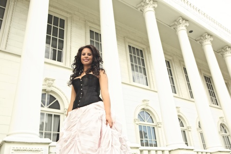 Glamorous young African American woman wearing a black bustier and full length puffy pink skirt poses in front of a white building with large columns and picture windows