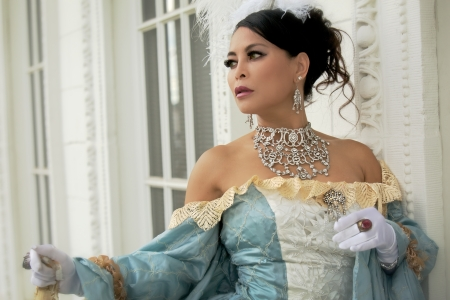 An Asian woman wearing a bejeweled chocker in an old fashioned style dress poses in front of a white building with ornate architectural details