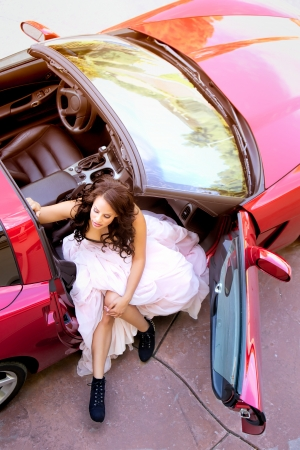 Overhead portrait of a glamorous young African American woman wearing a bustier and full length puffy pink skirt getting out of the passenger seat of a sports car with the top removed photo