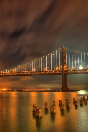 A dramatic sky over the San Francisco Bay Bridge, which is lit up at night from the  48,000 LED light sculpture by artist Leo Villareal, and the moon is reflected on the water  Фото со стока