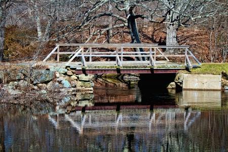 An East Coast wooden footbridge crosses over a calm reflective pond toward the end of winter Zdjęcie Seryjne