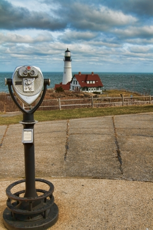 So  Portland Maine s Portland Headlight landmark lighthouse in the distance while standing next to old style public binoculars viewer Фото со стока