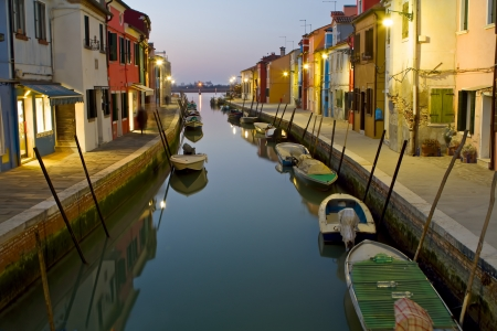 Burano, a small island about 45 minutes from historic Venice is characterized by the colorful buildings built along the small canals  This is a long exposure shot after sunset