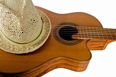 Straw Fedora Hat Rests Atop an Acoustical Guitar against a white background