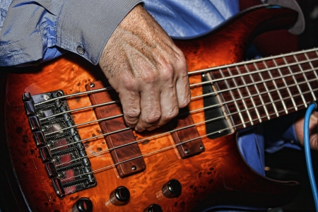 Man plays a 6-string electric Fender bass with a gorgeous orange swirl top