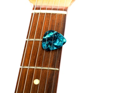 A guitar pick is placed between the strings of a electric guitar