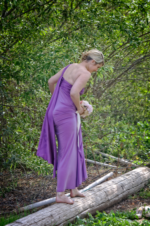 A young blond woman  possibly a bridesmaid  dressed in an elegant purple dress balances on a wooden log in the forest  park