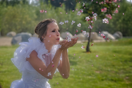 A beautiful young bride in a flowery and puffy wedding dress blows cherry blossoms in the air Zdjęcie Seryjne