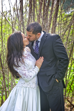 Still in wedding dress and suit, a young Hispanic couple kiss among a romantic setting of tall branches and twigs