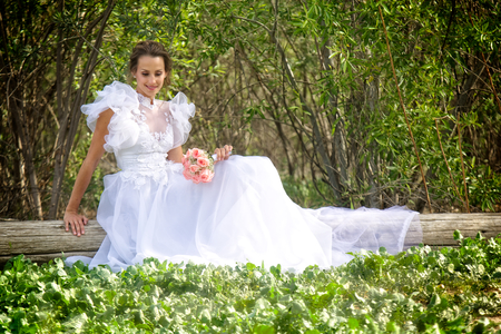 A smiling young bride dressed in a flowery and puffy white wedding dress sits on a wooden log in a grove of trees