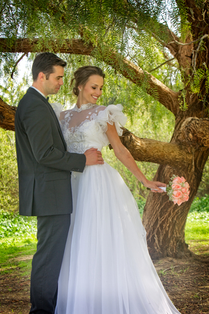 While standing under a large shade tree, a young attractive couple pose for their wedding day portrait