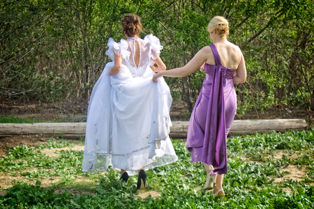 A young blond bridesmaid (Maiden of Honor) holds the skirt of a brides wedding dress as they walk toward a groove of trees.