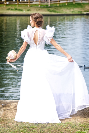 A young bride in a beautiful, flowing wedding dress with an open back and puffy sleeves stands by a pond in a park