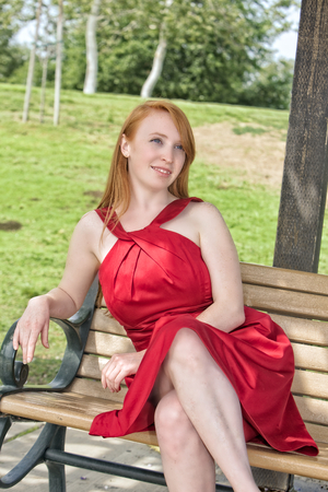 A young redhead woman sits on a park bench, wearing an elegant red dress, presumably for a special occasion