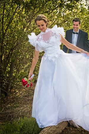 A young attractive Bridal couple walk along a wooden log, laughing and smiling