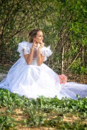 A smiling young bride dressed in a flowery and puffy white wedding dress looks out into the distance  her future  as she sits on a wooden log in a grove of trees