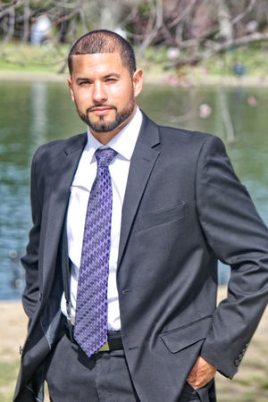 A Hispanic man with a well manicured beard and haircut, in suit and tie next to a pond at a park
